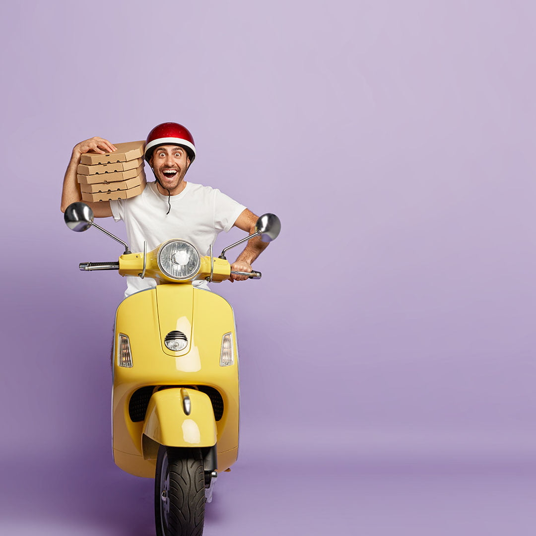 Overjoyed male delivery service courier has in depth knowledge of traffic regulations and routes, transports fresh baked pizza in cardboard containers, being on yellow scooter, has much work, orders